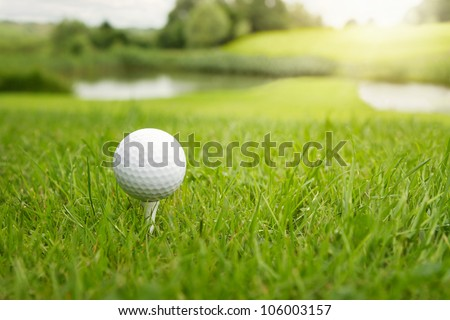 Golf ball on a tee against the golf course with copy space - stock photo