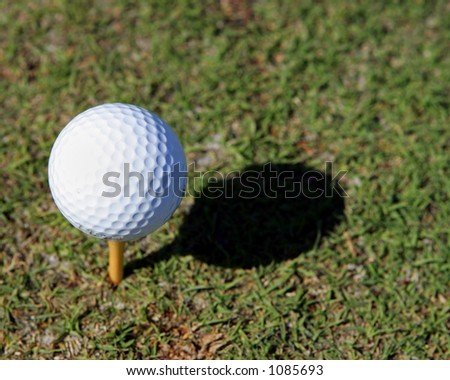 Golf ball on a tee with a shadow - stock photo
