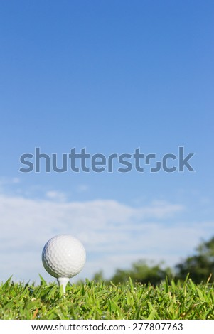 Golf ball on a tee with cloud and sky background - stock photo
