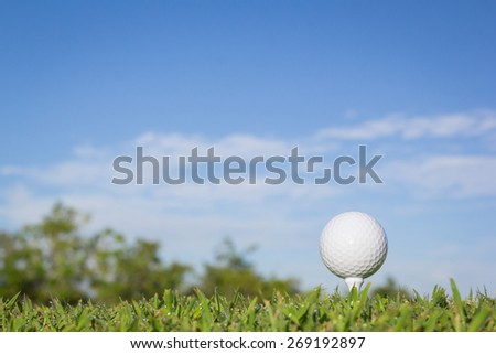 Golf ball on a tee with sky background - stock photo