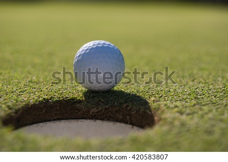 golf ball on edge of course hole representing achivement and success business concept - stock photo