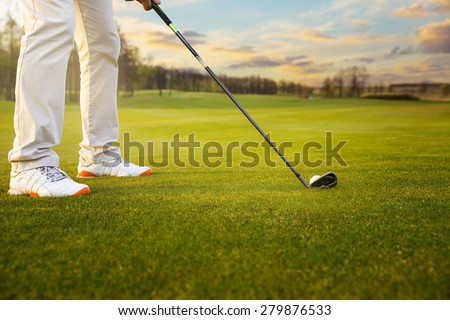 Golf ball on grass in front of golf club - stock photo