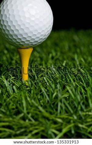 Golf ball on grass on black background. - stock photo