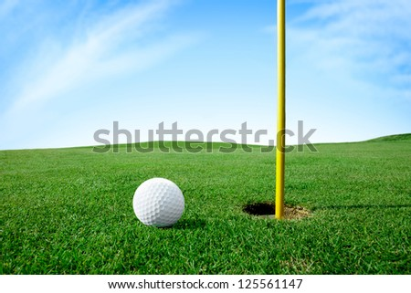 Golf ball on green grass next hole - stock photo