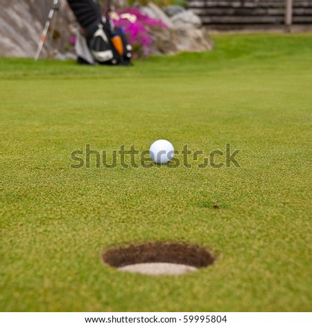 Golf ball on green with a hole. Shallow depth of field. Focus on the ball. - stock photo