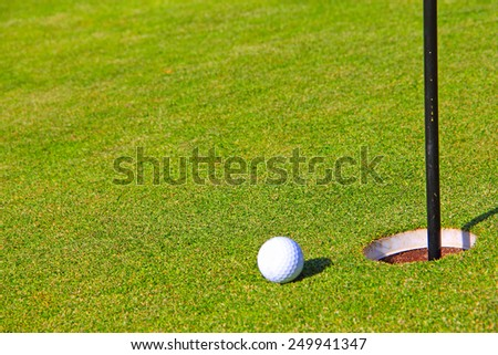 Golf ball on lip of cup close-up view - stock photo