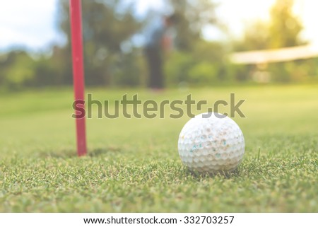 Golf ball on lip of hole , process in vintage style - stock photo