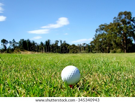 Golf Ball on orange tee with fairway and trees off in the distance - stock photo