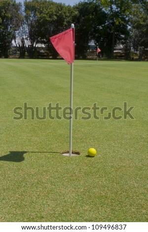 Golf ball on putting range near the hole - stock photo