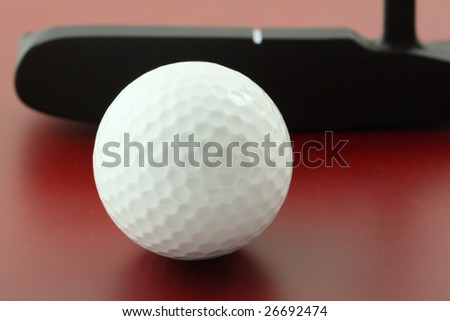 golf ball on red surface and club - stock photo