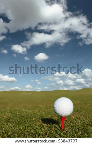 Golf ball on red tee with selective focus picking pick the ball - stock photo
