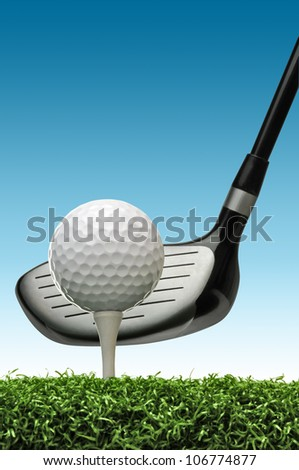 golf ball on tee about to be hit with a golf club - stock photo