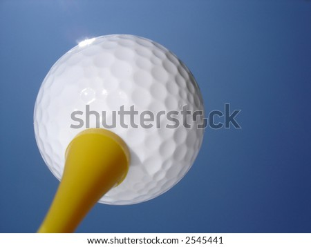 Golf ball on tee against blue sky background - stock photo