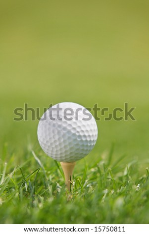 Golf Ball on Tee against green background of blurred  bright green grass. - stock photo