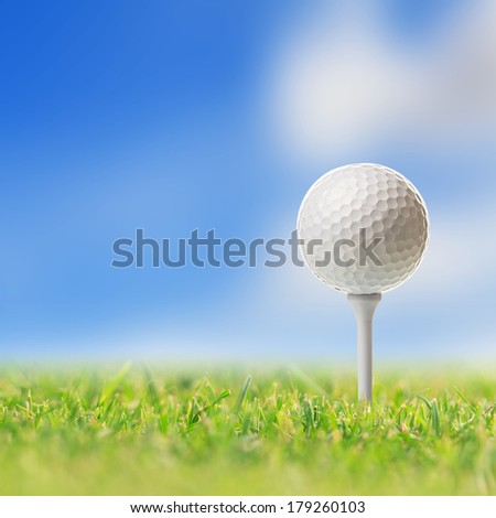Golf ball on tee in golf course - stock photo