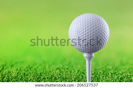 Golf ball on tee on green background - stock photo