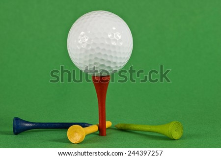 Golf Ball On Tee With Colored Tees Around On Green Background - stock photo