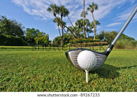 golf ball on tee with driver at tropical course, high res capture - stock photo