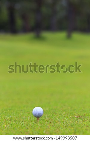 Golf ball on teeing area over a blurred green. Shallow depth of field. Focus on the ball.  - stock photo