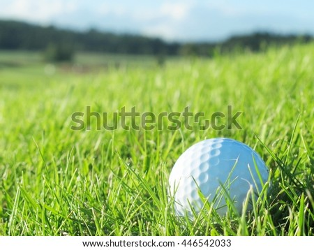 Golf ball on the green hill. Interesting course landscape In the background.  - stock photo