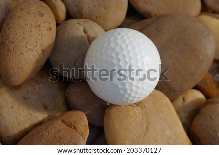 Golf ball on the rock, out the fairway - stock photo
