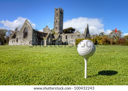 Golf ball on the tee - idyllic golf course of Adare and Franciscan Abbey in the background in Ireland. - stock photo