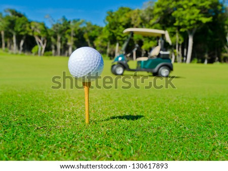 Golf ball on the tee with the golf cart out of the focus as a background.. - stock photo