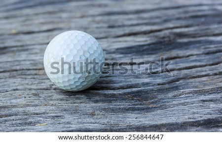 golf ball on the wood floor - stock photo