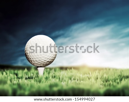 Golf ball placed on white golf tee on green grass golf course. Moody sunny sky. - stock photo