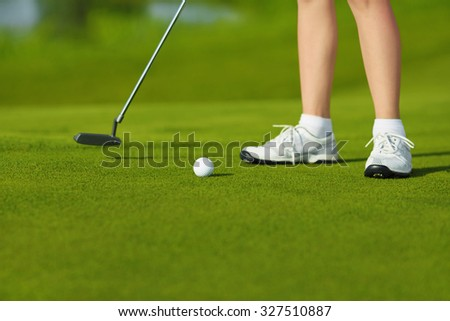 Golf ball, putter and boy's legs on green - stock photo
