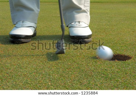 golf ball putting into hole - stock photo