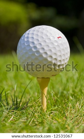 Golf ball resting on tee at golf course - stock photo