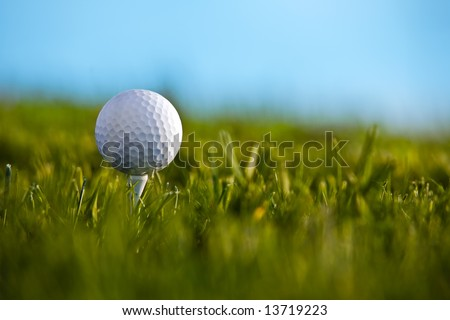 Golf ball sitting on tee with blue sky and grass background. - stock photo