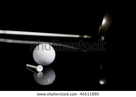 Golf ball, tee, and driver on black background with reflection - stock photo