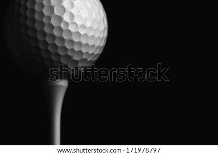 Golf Ball Teed Up Close Up against a Black Background; low key silhouette - stock photo