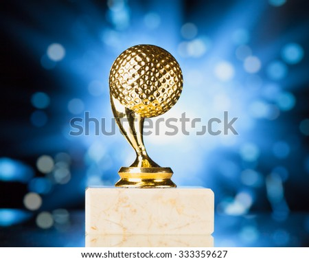 golf ball trophy against blue shiny sparks background - stock photo
