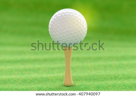 Golf ball with tee on artificial grass. - stock photo