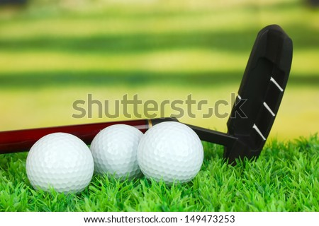 Golf balls and driver on green grass outdoor close up - stock photo