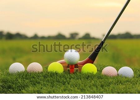Golf balls and wooden driver on green grass with sunset background - stock photo