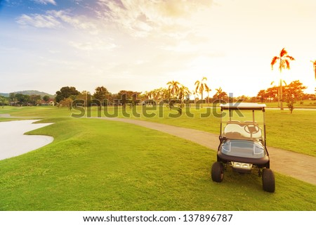 golf car with sun set in golf course. - stock photo