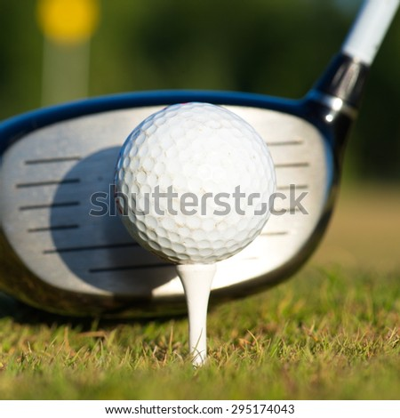 Golf club and ball on tee - stock photo