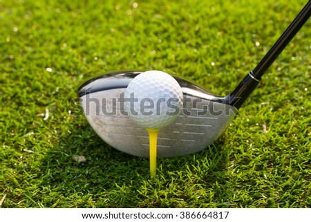 Golf club and Golf ball in tee on the grass - stock photo