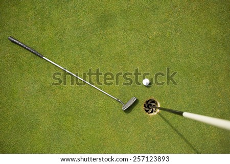 Golf club and golf ball on the putting green beside flag on a sunny day - stock photo
