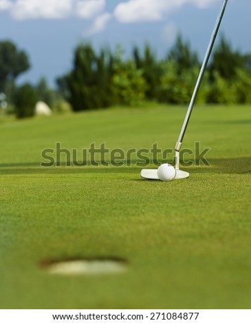 Golf club is ready for final putt on the green. - stock photo