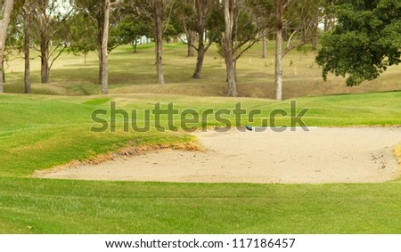 Golf coarse sand bunker with green grass - stock photo