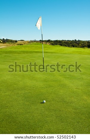 Golf course green with flag and ball in late afternoon sun - stock photo