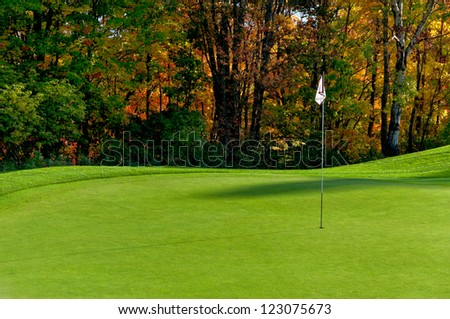 Golf course putting green with flag in autumn colors - stock photo