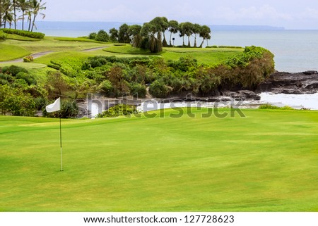Golf course with bunker and flag. Green fields of island - stock photo