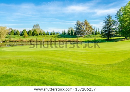 Golf course with gorgeous green and pond - stock photo