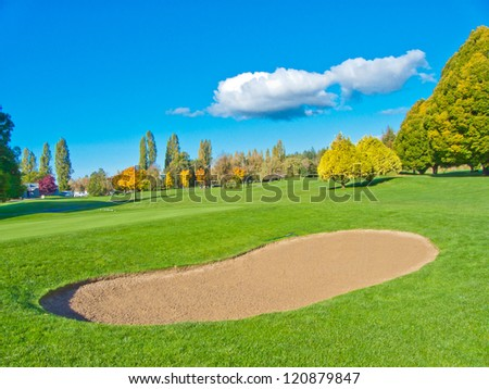 Golf course with gorgeous green and sand bunker and dark blue sky with white clouds as a background. - stock photo